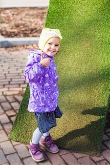 Una ragazza cammina per strada, in città, cavalca uno scooter, una passeggiata con la sua famiglia, infanzia, gioia, primavera