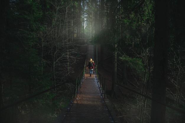 Ragazza cammina su un ponte sospeso su un fiume di montagna foresta mistica oscura