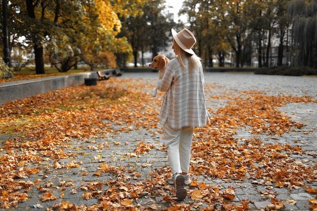 Una ragazza cammina tra le foglie in autunno con un cane in braccio.