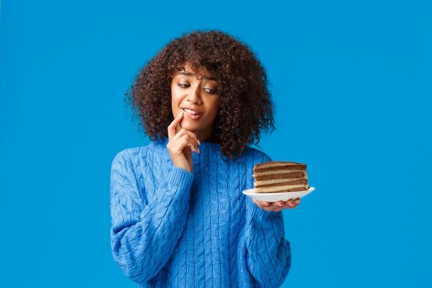 La ragazza vuole mangiare un pezzo delizioso ma preoccuparsi della dieta e delle calorie. la donna sciocca afroamericana attraente che prova a resistere alla tentazione prende il morso del dessert saporito, esaminante con desiderio il piatto