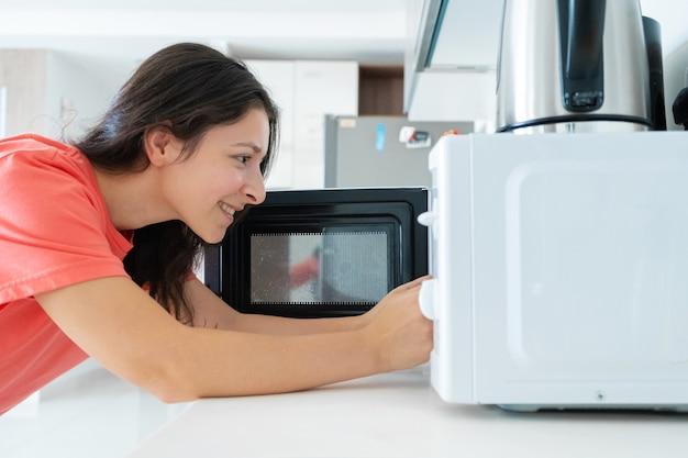 La ragazza riscalda il cibo nel microonde. uno spuntino veloce.