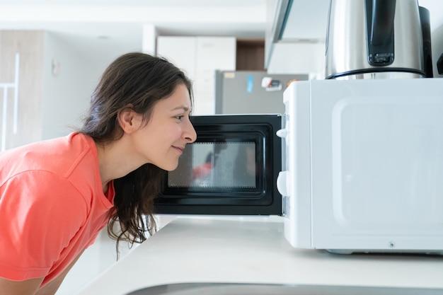 La ragazza riscalda il cibo nello spuntino veloce del microonde