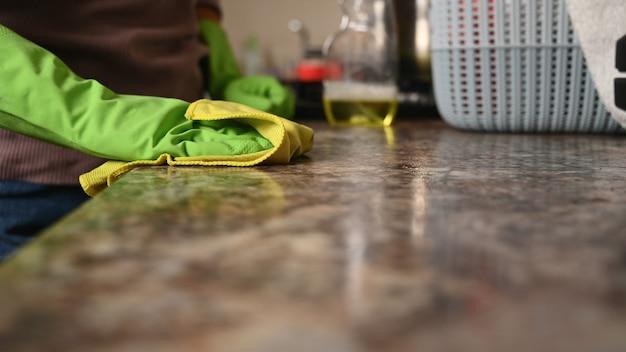 La ragazza lava il piano di lavoro in cucina.