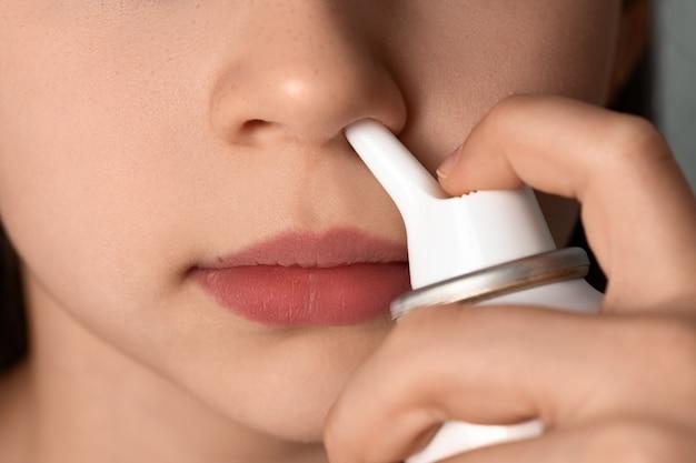 La ragazza si lava il naso con uno spruzzo di acqua di mare