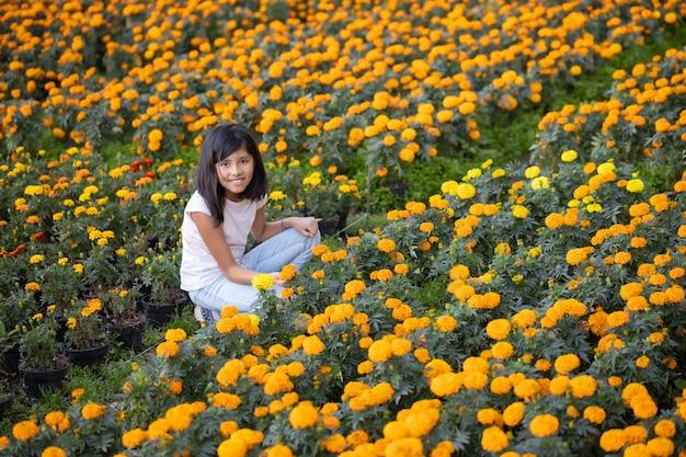 Ragazza che guarda e sorride ai fiori di cempasuchil