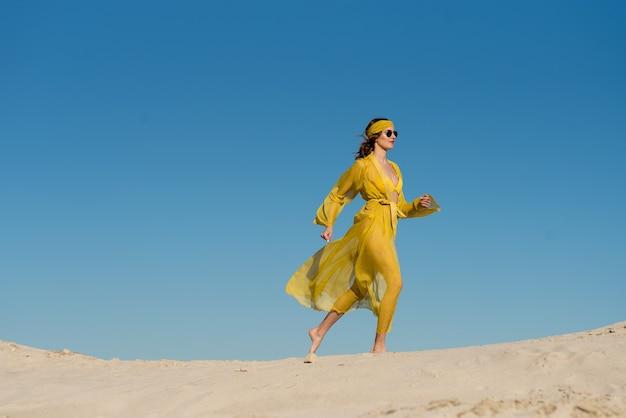 Ragazza che indossa abbigliamento da spiaggia e posa sulla spiaggia sabbiosa