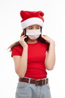 Ragazza che indossa abiti di natale maschera medica studio stile di vita vista ritagliata. foto di alta qualità