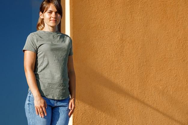 Ragazza che indossa una t-shirt bianca verde con spazio per il tuo logo, mock up o design nell'area urbana