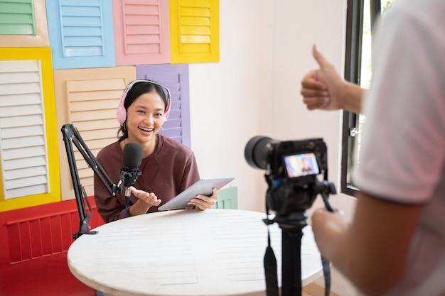 Una ragazza che indossa le cuffie davanti a un microfono mentre il cameraman in movimento pronto per iniziare la regi...