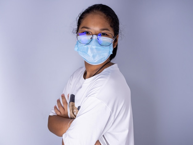 Ragazza che indossa una maschera e indossa occhiali in piedi con le braccia incrociate su uno sfondo bianco