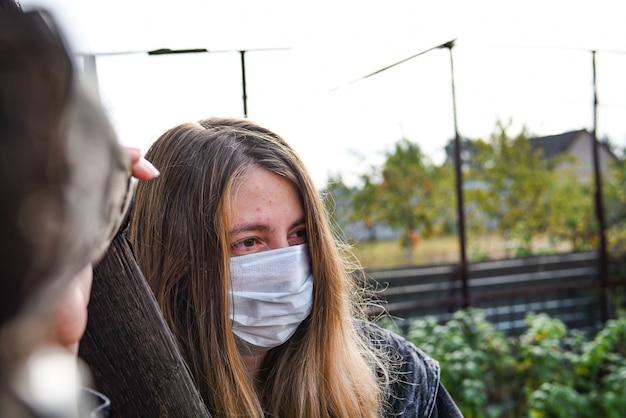 Ragazza che indossa una mascherina medica a causa dell'inquinamento atmosferico o dell'epidemia di virus in città. donna con maschera medica e facciale su un cielo blu.