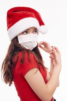 Ragazza che indossa una mascherina medica vestiti di natale cappello da babbo natale vacanza close-up sfondo chiaro