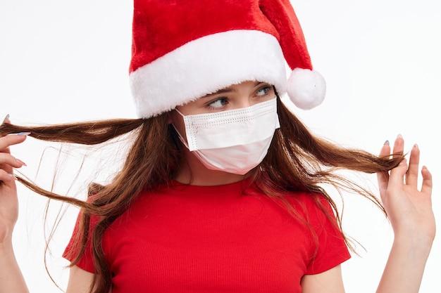 Ragazza che indossa una mascherina medica che tiene il suo primo piano i capelli di capodanno