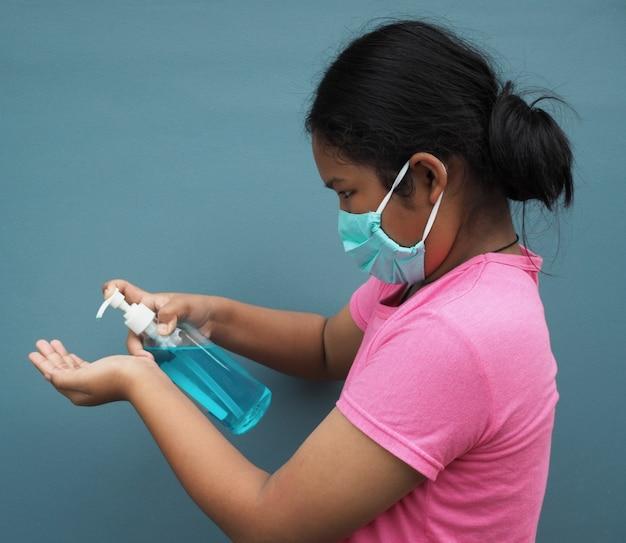 Una ragazza che indossa una maschera protettiva e premi il gel alcolico per lavarti le mani.