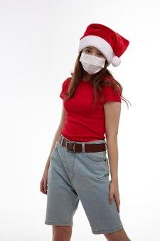 Ragazza che indossa un cappello da babbo natale rosso t-shirt protezione maschera medica nuovo anno