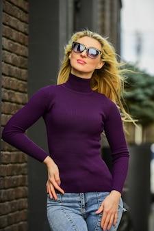 Ragazza che indossa abiti eleganti in posa all'esterno. ragazza all'aperto in autunno. modello di moda bruna in bei vestiti. indossare occhiali da sole alla moda. stile ragazza bionda in autunno o in primavera.