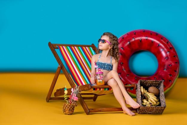 Ragazza che indossa gli occhiali da sole del costume da bagno che tiene vaso con succo o gallo