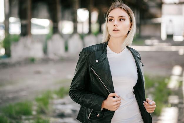 Ragazza che indossa t-shirt e giacca di pelle in posa contro la strada