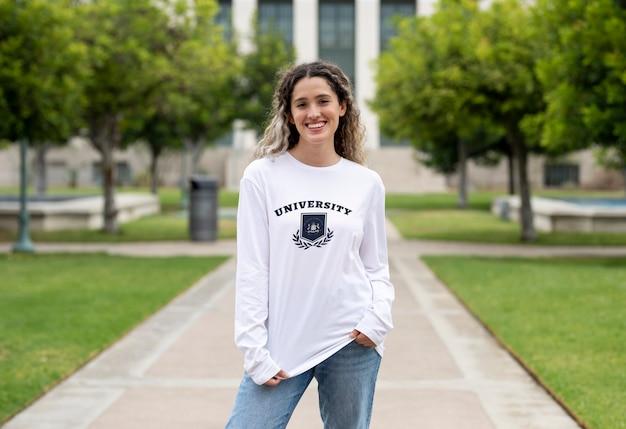 Ragazza che indossa un maglione universitario al campus, abbigliamento universitario