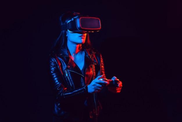 Ragazza che indossa occhiali per realtà virtuale con luci rosse e blu su sfondo nero