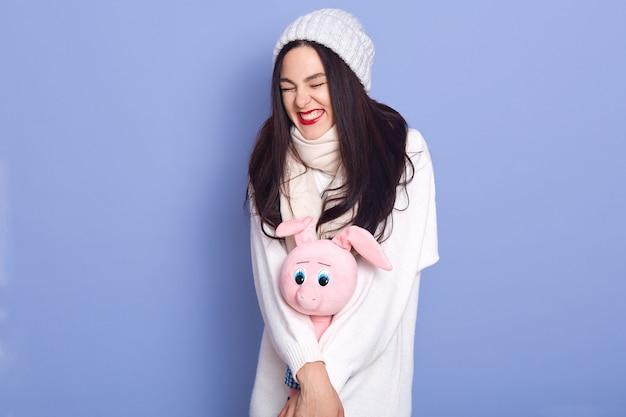 Ragazza che indossa cappello bianco, maglione e sciarpa tenendo il maiale giocattolo rosa, pronto a festeggiare il natale