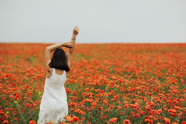 Ragazza che indossa un abito bianco in piedi nel mezzo di un campo pieno di papaveri rossi