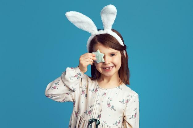 La ragazza indossa orecchie da coniglio copre l'occhio con un biscotto a forma di stella isolato sopra il blu
