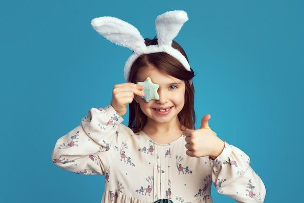 La ragazza indossa le orecchie da coniglio copre l'occhio con un biscotto a forma di stella e mostra il pollice in su
