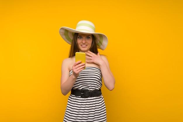 La ragazza indossa un cappello di paglia e un vestito a strisce bianche corte con le spalle aperte sorpresa dalla notizia su uno smartphone
