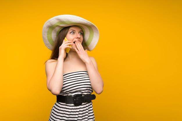 La ragazza indossa cappello di paglia e brevi strisce bianche si veste con le spalle aperte parlando su uno smartphone