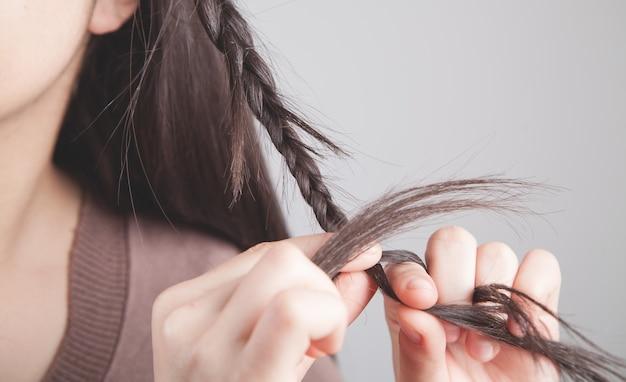 Ragazza che tesse i suoi capelli su una treccia.