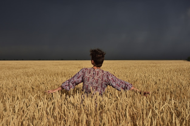 Ragazza in un campo di grano prima di un temporale