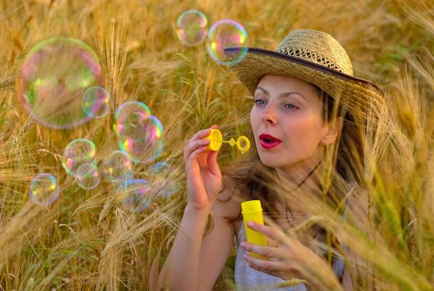 Ragazza nel campo di grano in abito bianco e cappello stetson che soffia bolle di sapone. messa a fuoco selettiva.