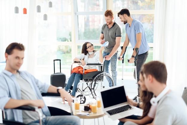 Ragazza in sedia a rotelle e disabili sono in piedi nel corridoio dell'aeroporto