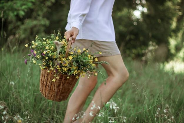 Una ragazza con una camicetta bianca tiene in mano un cesto di vimini con un mazzo di fiori selvatici. passeggiata estiva nel campo. primo piano delle gambe di una donna che cammina in un campo con un cesto di fiori