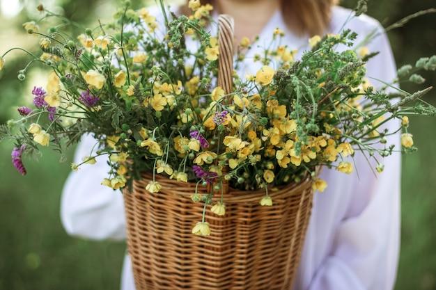 Una ragazza con una camicetta bianca tiene in mano un cesto di vimini con un mazzo di fiori selvatici. passeggiata estiva nel campo. sezione centrale
