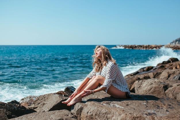 Una ragazza con una camicetta bianca si siede sulle pietre vicino al mare