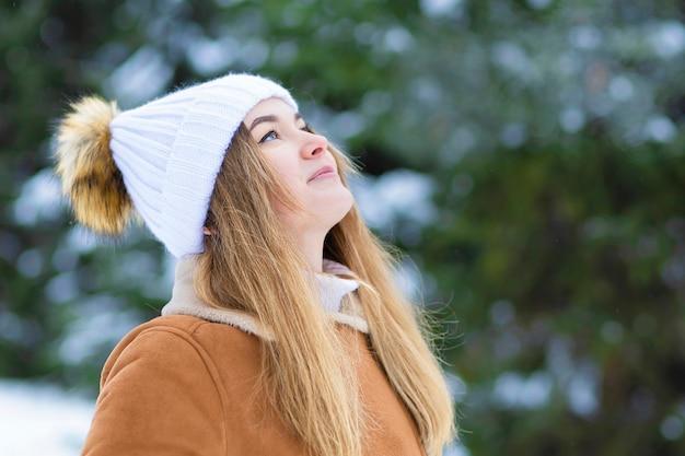 Ragazza in abiti bianchi in inverno nevoso giorno nella foresta. giovane donna che sorride, gioca con la neve, si gode la natura, respira aria pulita e gelida