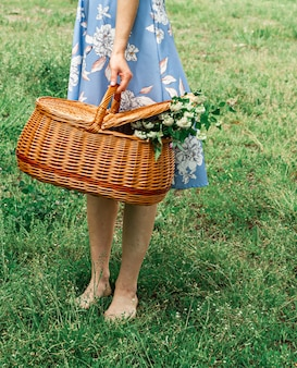 Ragazza in abiti bianchi con cesto di fiori in bouquet estivo da giardino in stile bohochic