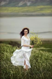 Una ragazza in abito bianco, con un cappello elegante e un bouquet di fiori di campo gialli