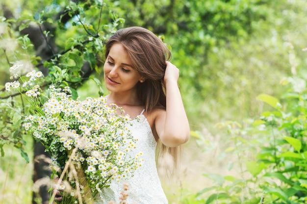 Ragazza in un vestito bianco che tiene il mazzo di fiori e vegetazione.