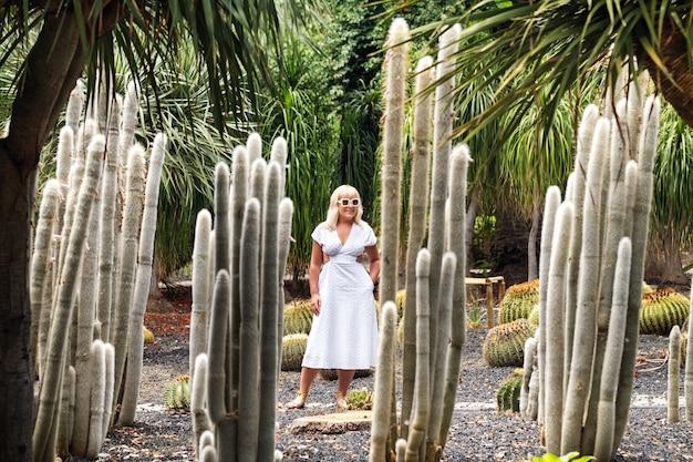 Una ragazza in abito bianco su enormi cactus sull'isola di tenerife, spagna.