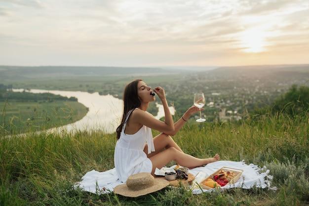 Ragazza in vestito bianco che si siede sulla coperta bianca di picnic che beve vino e che mangia le ciliegie fresche.