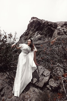 Una ragazza vestita di bianco, scalza, mise il piede su una pietra, tra le rocce