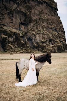 Una ragazza in abito bianco accanto a un cavallo bianco