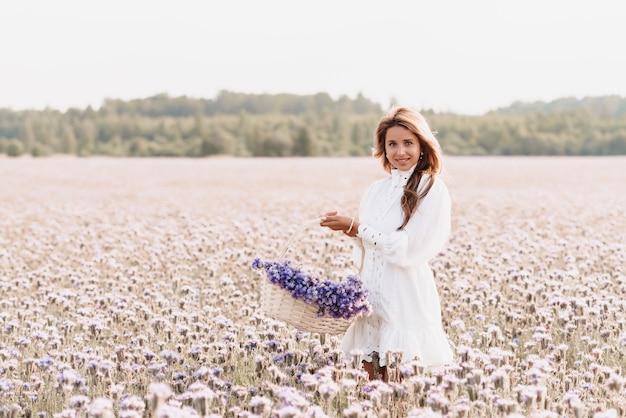 Ragazza in un abito bianco con un mazzo di fiori in un cesto