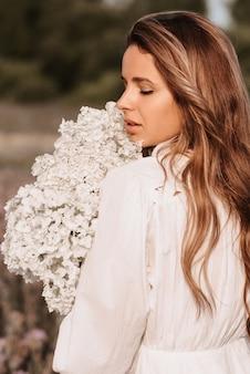 Ragazza in un abito bianco con un mazzo di fiori in estate