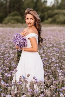 Ragazza in un abito bianco con un mazzo di fiori viola in un campo in natura in estate