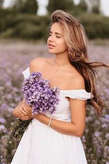 Ragazza in un abito bianco con un mazzo di fiori viola in un campo