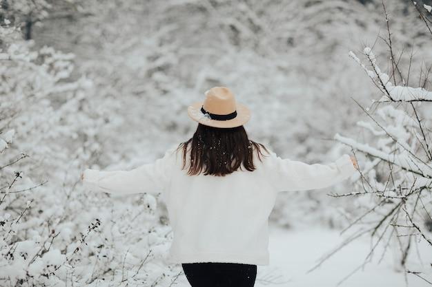Una ragazza con una pelliccia bianca e un cappello beige si sta divertendo in un bosco innevato da favola. alberi innevati.
